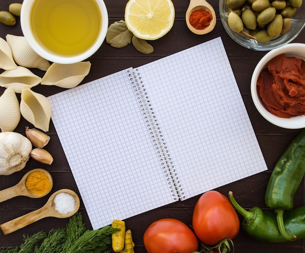 Open notitieboekje omringd door voedselingrediënten. culinaire achtergrond voor recepten.