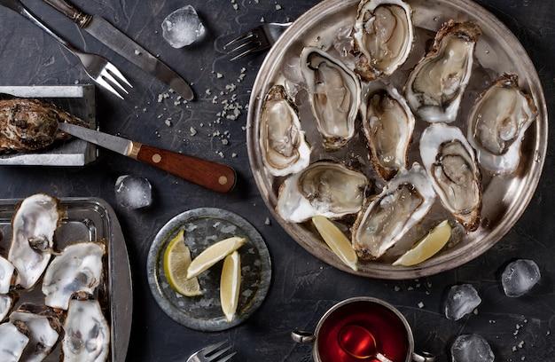 Open oesters op een bord met plakjes citroen en ijs. bovenaanzicht