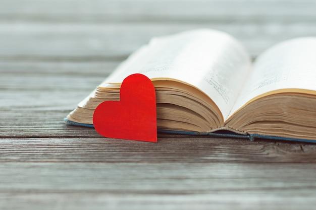 Open oud boek en rood papier hart op houten tafel