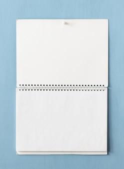 Open papieren album met lege pagina's op veren hangt aan de muur.