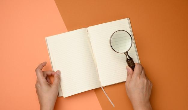 Open papieren notitieblok met lege witte lakens en een houten vergrootglas op een oranje achtergrond. achtergrond voor inscripties, zoeken naar oplossingen en antwoorden