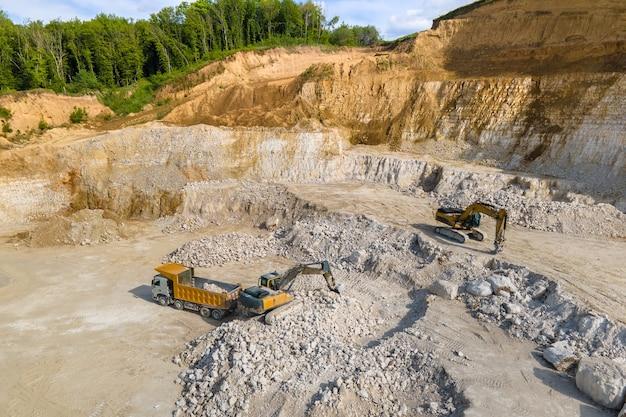 Open pit mining van bouwzandsteenmaterialen met graafmachines en dumptrucks.