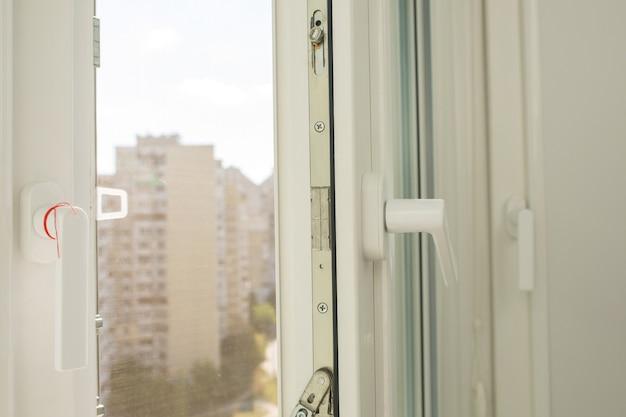 Open plastic vinylraam met uitzicht op flatgebouwen met meerdere verdiepingen op zonnige dag