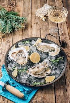 Open rauwe oesters met citroen en rozemarijn. verse zeevruchten op een metalen dienblad op een rustieke houten achtergrond. kerst versiering