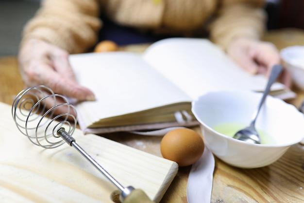 Open receptenboek in de handen van een oudere vrouw voor een tafel met keukengerei
