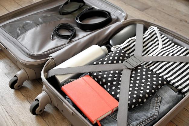 Open reiskoffer vol kleren geïsoleerd op houten oppervlak