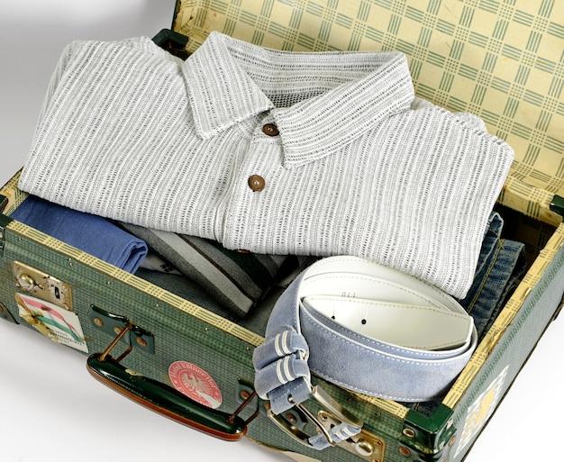 Open retro koffer verpakt voor reis met herenkleding
