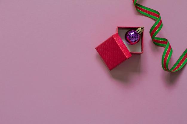 Open rode geschenkdoos en paarse kerst zeepbel binnen