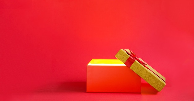 Open rode geschenkdoos met een strik met een gouden gloed en glitter binnen op een rode achtergrond, banner, copyspace