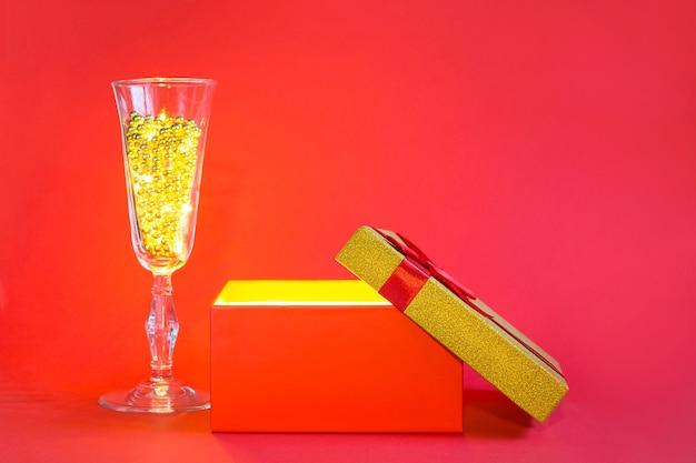 Open rode geschenkdoos met gouden gloed en glitter binnen en champagne glas met bubbel kralen, banner, copyspace