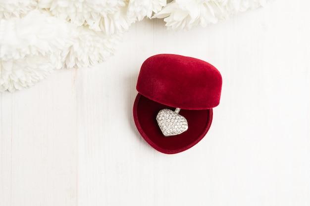 Open rode geschenkdoos met hartvormige hanger van zilver of witgoud