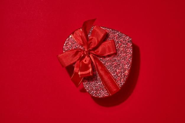 Open rode hartdoos, lint en verspreide harten in de buurt op dieprode achtergrond. valentijnsdag briefkaart of concept. ruimte voor tekst. bovenaanzicht.