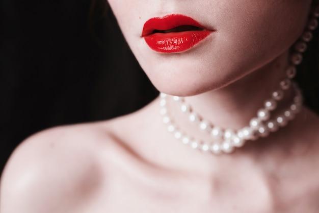 Open rode lippen en parels rond de nek op een zwarte achtergrond. elegante vrouwelijke portret in retro stijl. fetisj seksueel concept. mode portret van een jong meisje close-up.