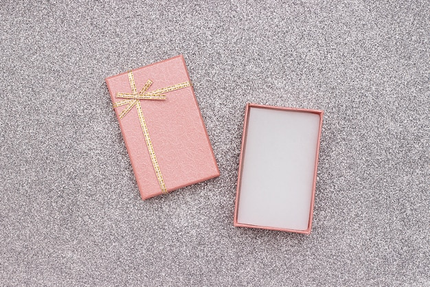 Open roze geschenkdoos met strik op zilveren glanzende achtergrond in minimalistische stijl mockup