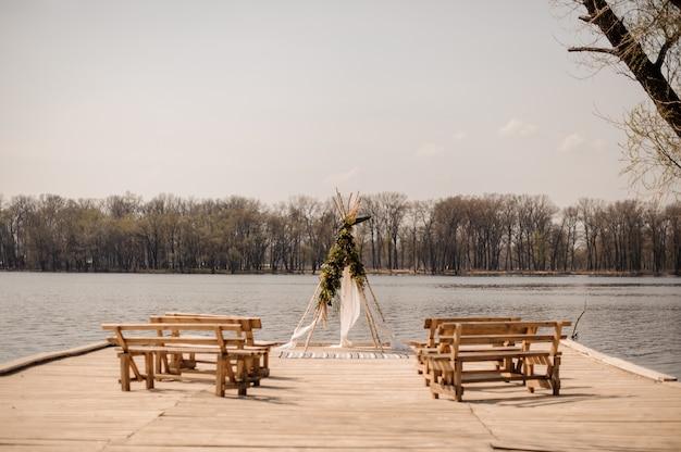Open ruimte voor europese huwelijksceremonie met houten banken en handgemaakte boog versierd met tropische bloemen