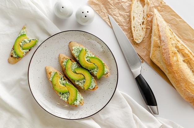 Open sandwiches gemaakt van vers frans stokbrood, ricotta en spinazie op witte tafel. ontbijt concept. overhead, plat liggen