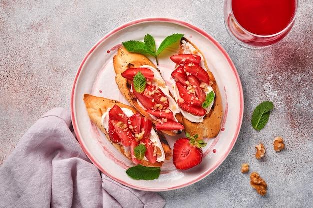 Open sandwiches met aardbeien, zachte kaasmunt en walnoot in keramische plaat op een lichtgrijze stenen ondergrond. zomer en gezond dieet, vegetarisch voedselconcept. bovenaanzicht.