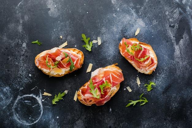 Open sandwiches met jamon, rucola en harde kaas op een betonnen oude donkere ondergrond