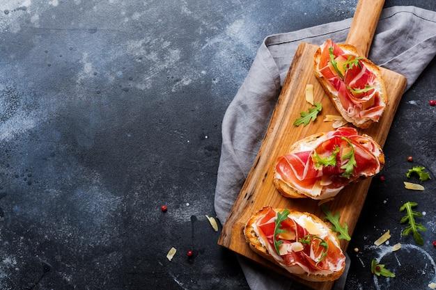 Open sandwiches met jamon, rucola en harde kaas op een houten standaard op een betonnen oude donkere ondergrond