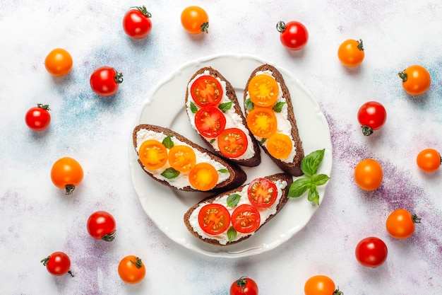 Open sandwiches met kwark, cherrytomaatjes en basilicum.