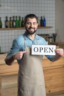Open. slimme enthousiaste jonge eigenaar van een café die zich opgewonden voelt na het openen van een geweldig comfortabel café terwijl hij met het bord staat en glimlacht