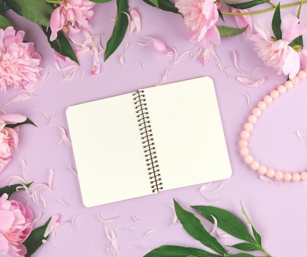 Open spiraalvormig notitieboekje met lege witte pagina's op purpere, bloeiende roze pioenen