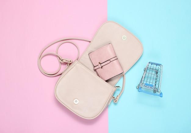 Open stijlvolle leren tas met een portemonnee en een miniatuur trolley om op pastel te kopen.