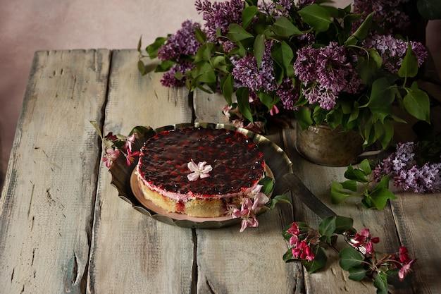 Open taart met bessengelei en bessen op een vintage schaaltje. stilleven met takken van lila
