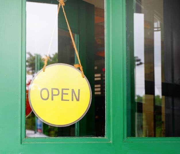 Open teken boord gele opknoping op houten deur café