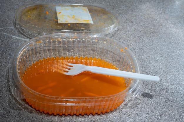 Open transparante plastic container met overgebleven koreaanse wortelen en een plastic lepel tegen een grijze achtergrond, kopieer ruimte. fastfood-concept. recyclingconcept voor plastic kookgerei