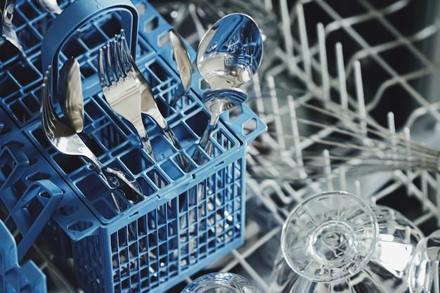 Open vaatwasser machine met schoon serviesgoed in de keuken, close-up