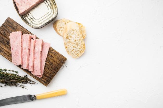 Open varkensvlees lunchworst kan met stokbrood set, op witte stenen tafel achtergrond, bovenaanzicht plat lag, met kopieerruimte voor tekst