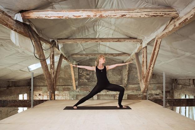 Open voor de wereld. een jonge atletische vrouw oefent yoga op een verlaten bouwgebouw. geestelijke, lichamelijke gezondheid. concept van een gezonde levensstijl, sport, activiteit, gewichtsverlies, concentratie.