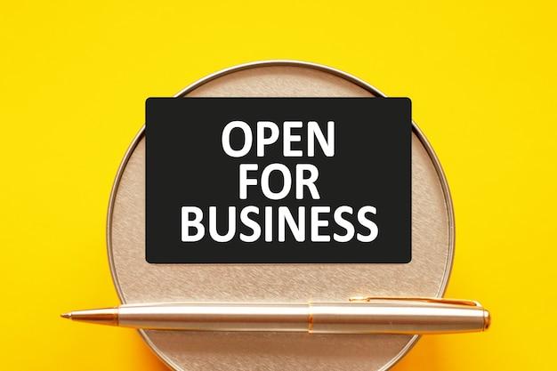 Open voor zaken - woorden schrijven witte letters op een vel papier. zwarte kaart met tekst op een gele muur met ronde metalen standaard en metalen schrijfpen. bedrijfs-, financiële en onderwijsconcept