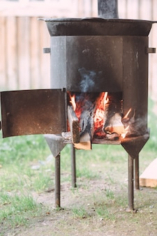 Open vuurhaard van werfketel, met brandhout erin