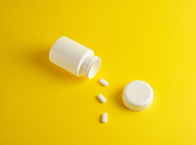 Open witte plastic pot voor medicijnen en ovale pillen