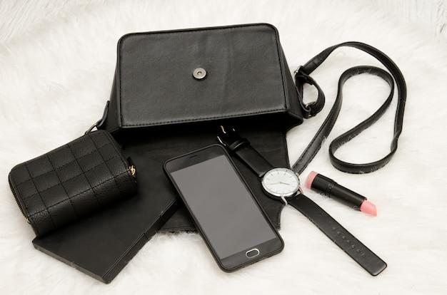 Open zwarte tas met gevallen spullen, notebook, mobiele telefoon, horloge, tas en lippenstift. de witte vacht op achtergrond, bovenaanzicht