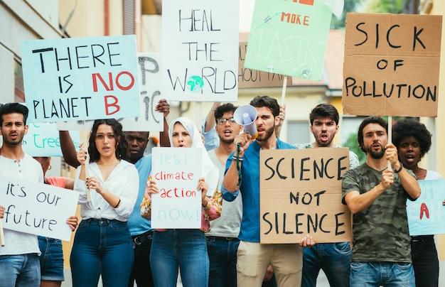 Openbare demonstratie op straat tegen de opwarming van de aarde en vervuiling. groep multi-etnische mensen die protesteren tegen klimaatverandering en plastic problemen in de oceanen