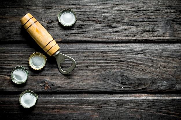 Opener met deksels van bierflesjes. op zwarte houten achtergrond