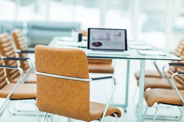 Opengeklapte laptopcomputer met financiële grafieken op tafel met de manager in een modern kantoor. de foto is een lege ruimte voor uw tekst