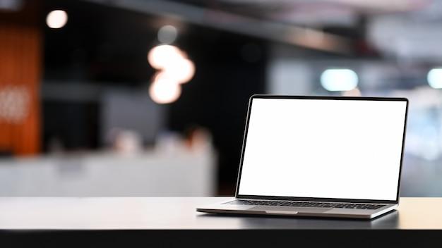 Opengeklapte laptopcomputer met leeg scherm op witte tafel en vergaderruimte wazig achtergrond.