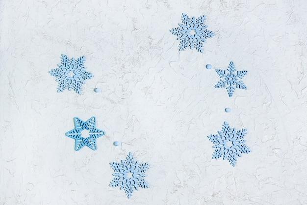Opengewerkte houten blauwe sneeuwvlokken op lichte glanzende achtergrond met copyspace. mooie decoratie voor kerstmis of nieuwjaar. bovenaanzicht plat leggen.