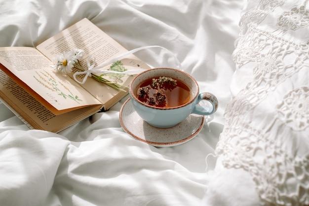 Opengewerkte kant, katoenen witte deken. boek plantkunde, mok met natuurlijke kruidenthee gemaakt van munt, zomer madeliefjebloemen. ochtendontbijt op bed. provence en retrostijl. schone gezelligheid en frisheid.