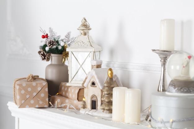 Openhaardmantel is versierd voor kerstmis met slinger, lichten, een strik en andere decoraties.
