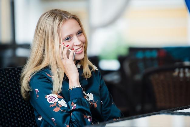 Openhartig beeld van jonge vrouw die op de telefoon in een koffie spreekt. selectieve aandacht.