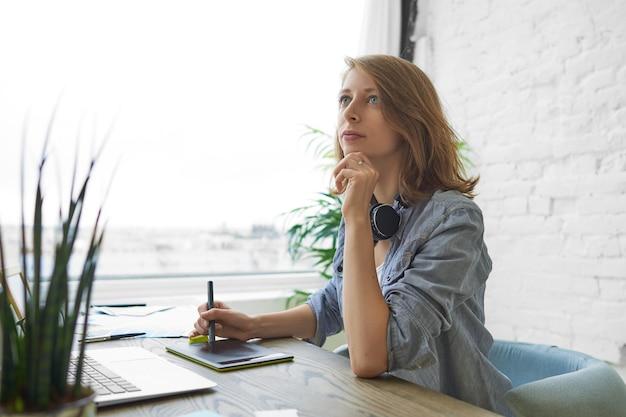 Openhartig schot van aantrekkelijke bekwame jonge vrouwelijke ontwerper zit aan bureau voor opengeklapte laptop, pen vasthouden terwijl puttend uit grafisch tablet, bezig met interieur ontwerpproject thuis kantoor