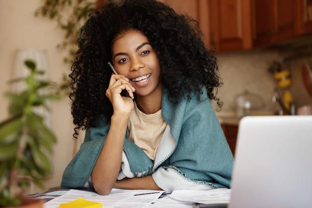 Openhartig schot van aantrekkelijke jonge afrikaanse vrouw met krullend haar die omslag dragen die op mobiele telefoon spreekt