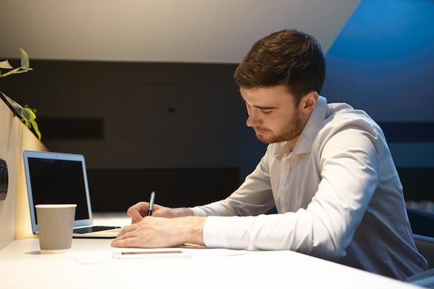 Openhartig schot van geconcentreerde jonge kaukasische creatieve mannelijke werknemer met baard die in bureau werken
