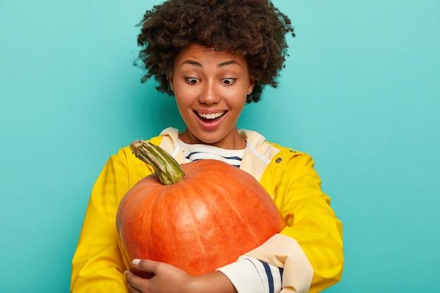 Openhartig schot van gelukkig gemengd ras jonge vrouw omhelst grote pompoen, gekleed in gele regenjas, verheugd enorme groente te kweken in eigen tuin, modellen tegen blauwe achtergrond. herfst decoratie.