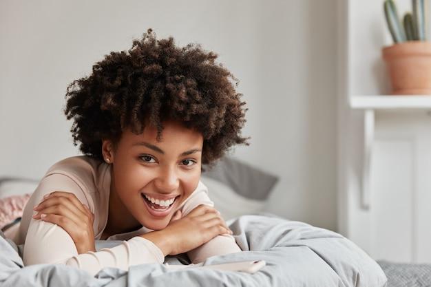 Openhartig schot van het aangename jonge vrouw stellen thuis in comfortabel bed